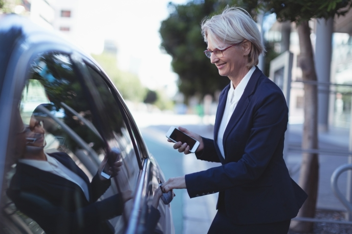 Businesswoman opening car door